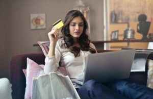 rsz 1rsz woman holding card while operating silver laptop 919436